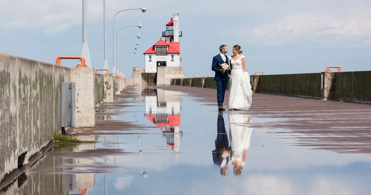 Bride and groom photo walking outside with rain reflecting off pavement.