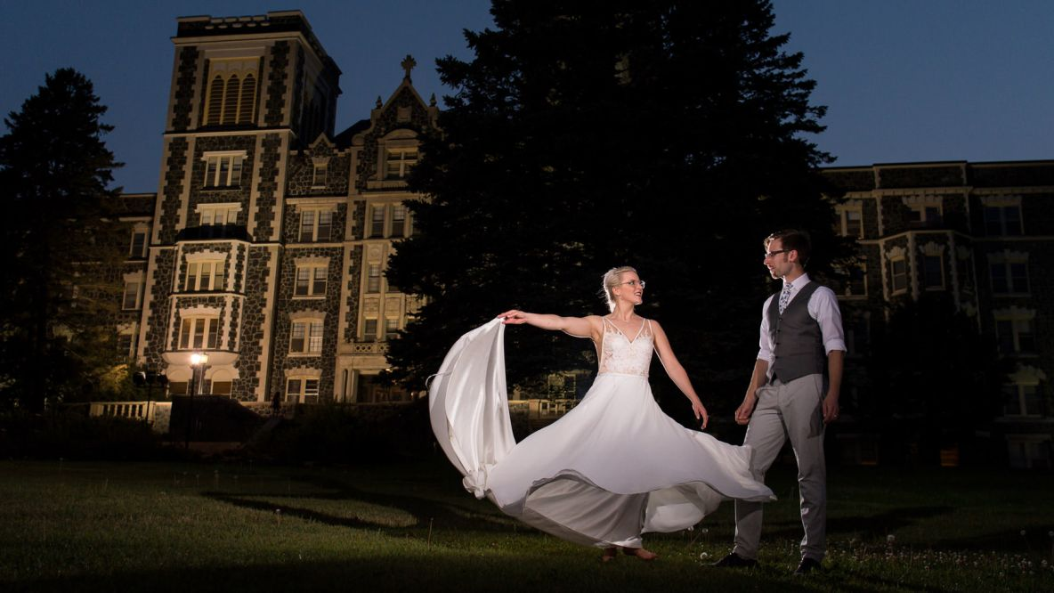 Sara and Eric and night in front of Tower Hall.