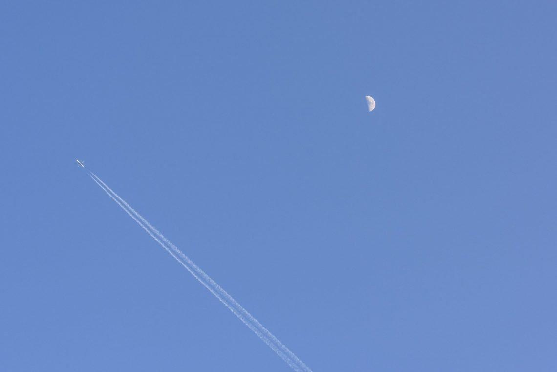 Plane moon and vapor trails