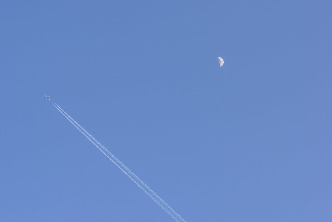 Plane moon and vapor trails