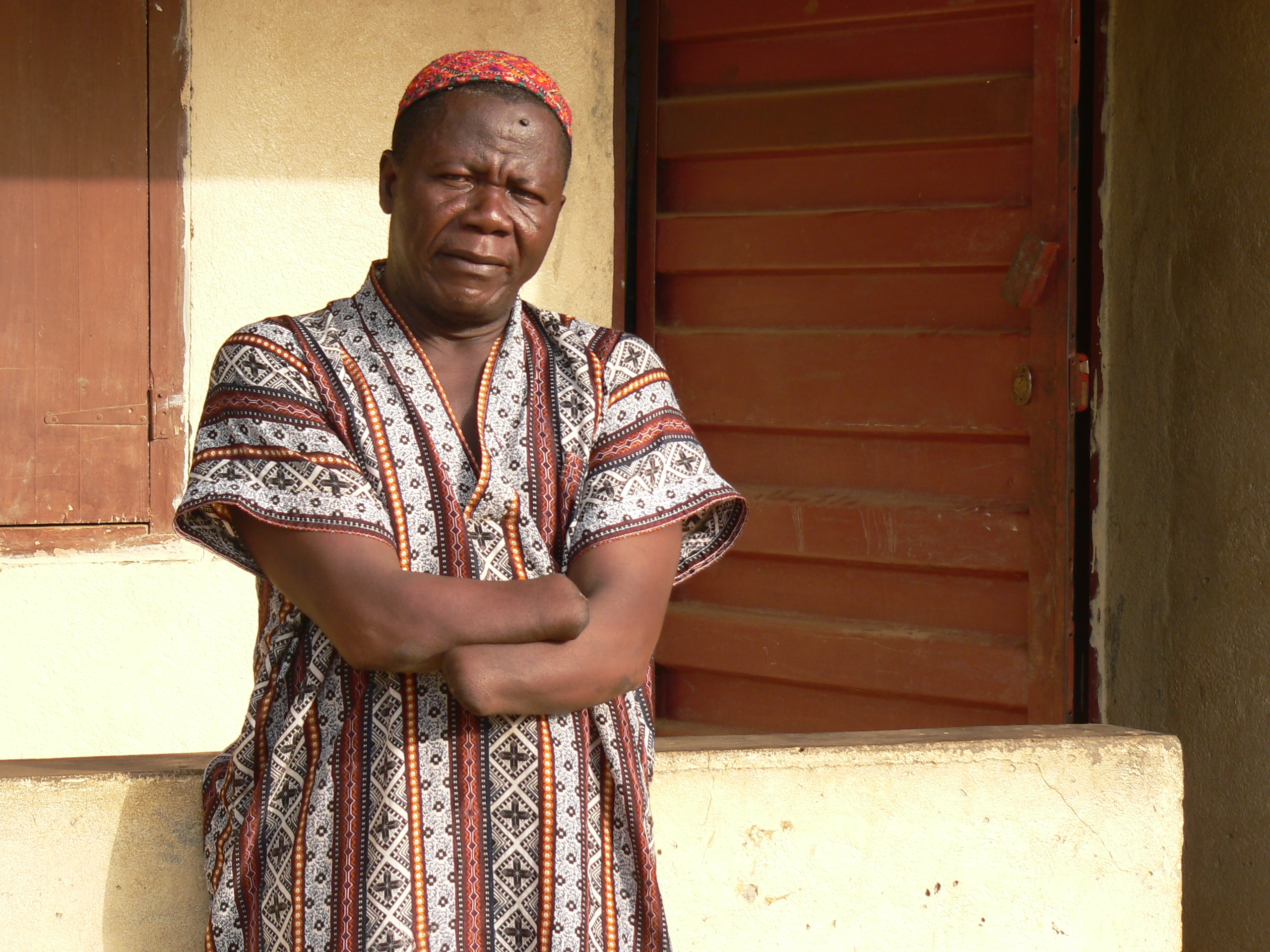 Lamin Jusu Jaka, chair of Sierra Leone's Amputees and War Wounded Association, stands in front of his house in Freetown, Sierra Leone.