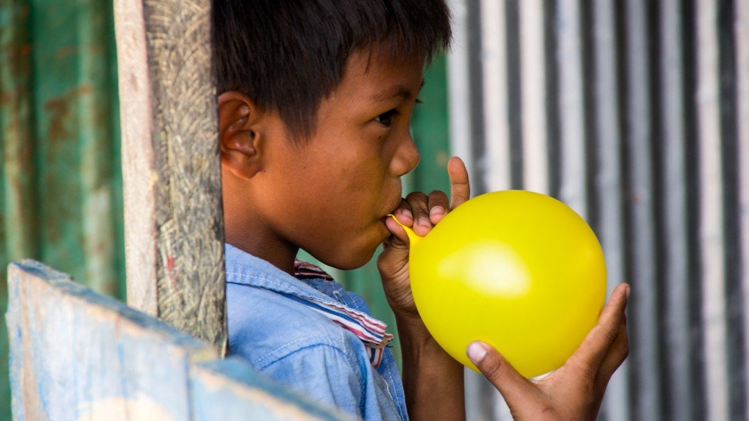 A male student blowing up a balloon for a class party at CESHEO Svay Thom campus near Siem Reap, Cambodia