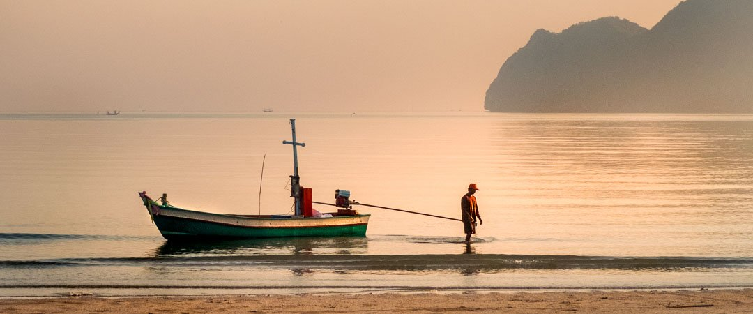 A fisherman brings his boat in to shore, Sam Roi Yot, thailand