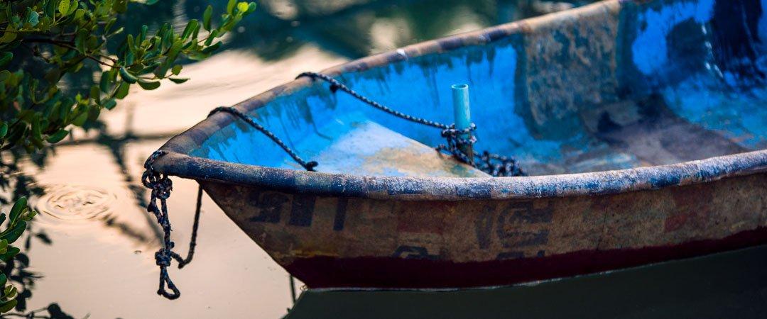 A blue boat rests in a small marina near Sam Roi Yot beach Thailand