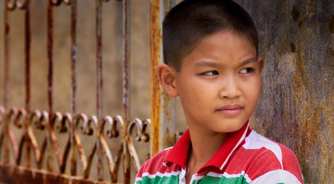 Vietnamese Child posing by a gate near Hanoi, Vietnam