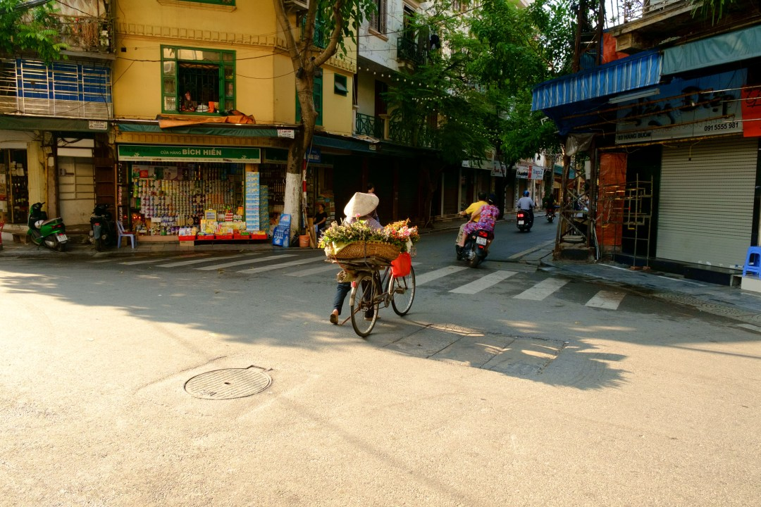 Woman pushing a bike through an intersection - Old French Quarter, Hanoi, Vietnam