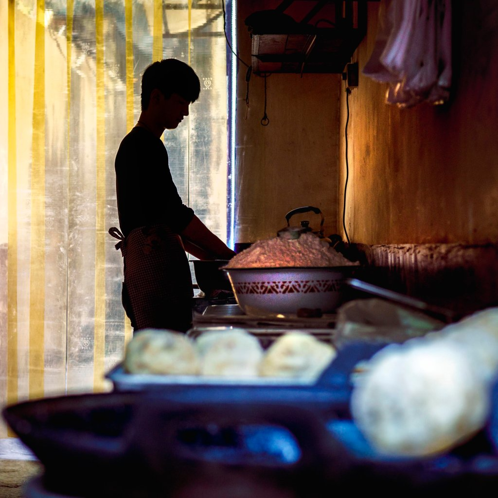 Photo of a man making dumplings in Xi'an China's muslim quarter by humanitarian photographer Bryon Lippincott