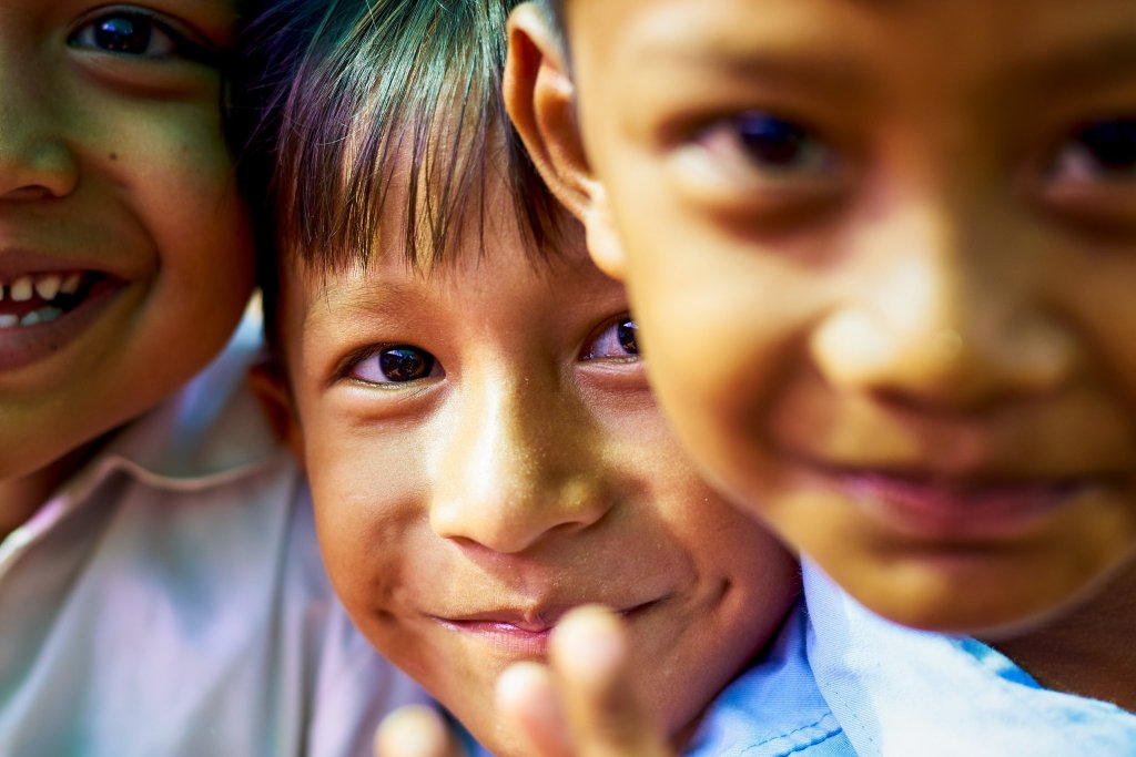 photo of 3 cambodian boys posing for the camera by Humanitarian Photographer Bryon Lippincott