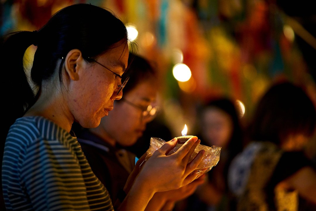 Photo of women lighting candles and placing them at the local Buddhist Wat during the Loi Krathong festival in Chiang Mai, Thailand  on November 11, 2019 by photographer Bryon Lippincott