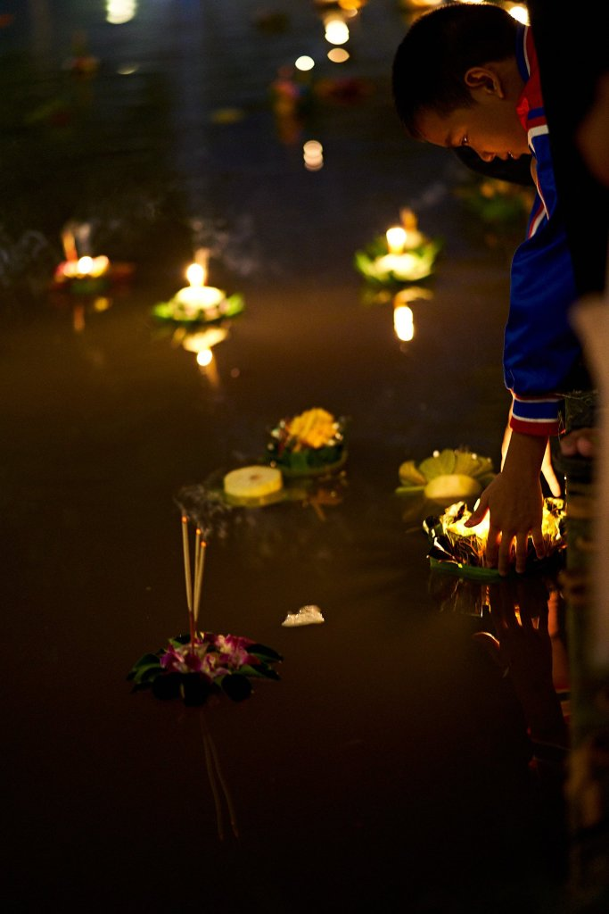 Photo of a boy gently pushing is Krathong out into the water in Chiang Mai, Thailand during the Loi Krathong festival on November 11, 2019 by photographer Bryon Lippincott