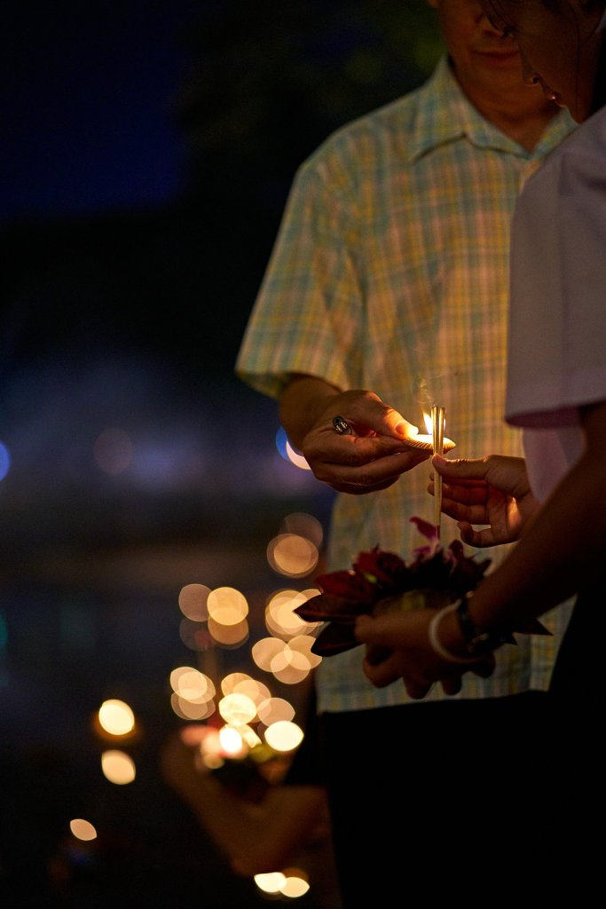 Photo of a father lighting the incense on his daughters Krathong with a small candle in Chiang Mai, Thailand during the Loi Krathong Festival on November 11, 2019 by Bryon Lippincott