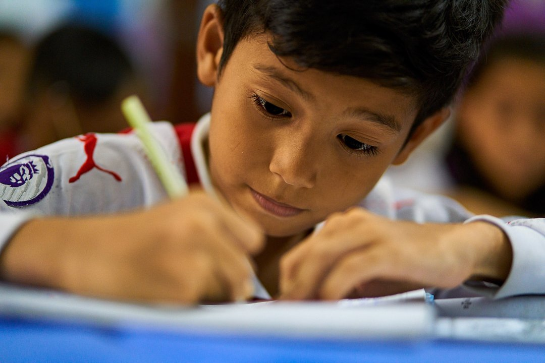 photo of a student writing for an assignment in class at New Life School in Phnom Penh, Cambodia.