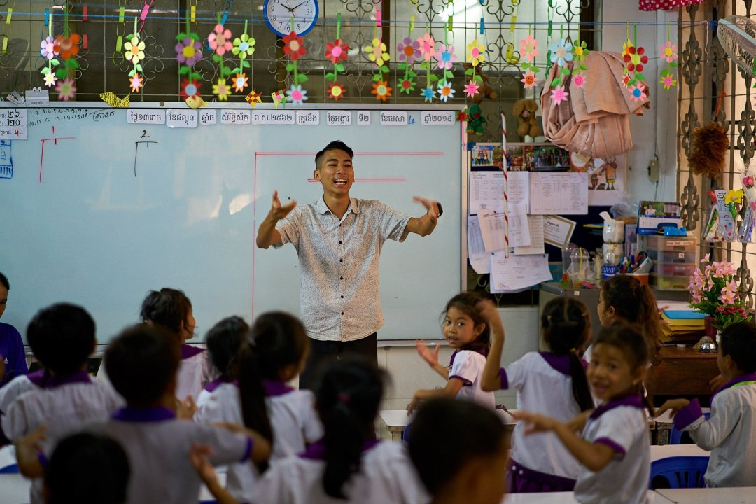 Photo of English Teacher Yin Pireach teaching students at New Life School in Phnom Penh, Cambodia by humanitarian photographer Bryon Lippincott