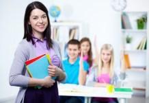 szczęśliwy nauczyciel - w tle klasa szkolna i uczniowie