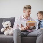 ojciec z synem siedzą na sofie, ojciec czyta mu książkę