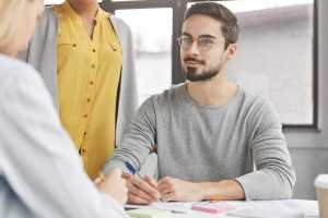 Bearded male employer communicates with job applicant, conducts interview with expert in economy fie