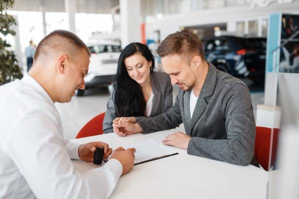 Salesman and couple make out the sale of a new car