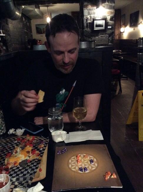 Bill plays Sinoda at a restaurant table.