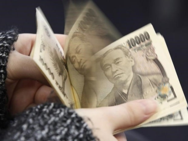 A woman counts Japanese 10,000 yen notes in Tokyo. Photo: Reuters
