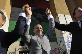French President Nicholas Sarkozy, left, Libya's NTC leader Mustafa Abdul-Jalil, center, and British Prime Minister David Cameron, right, gesture during their visit to Benghazi, Libya, Thursday, Sept. 15, 2011. Cameron and Sarkozy gave Libya's new rulers strong support during a landmark visit to Tripoli on Thursday, vowing to release billions of dollars more in frozen assets and to push ahead with NATO strikes against Moammar Gadhafi's last strongholds. (AP Photo/Philippe Wojazer, Pool)