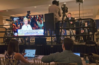 Democratic presidential candidate Hillary Clinton is seen on a television monitor addressing her supporters, as reporters file their stories after a June 7 news conference by presumptive Republican nominee Donald Trump. (Mary Altaffer / AP)