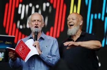 Labour party leader Jeremy Corbyn addresses the crowd alongside Glastonbury organiser Michael Eavis on the Pyramid Stage as he makes a guest appearance at the Glastonbury Festival Site, 24 June 2017 (Getty Images)