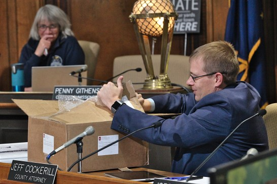 Monroe County attorney, Jeff Cockerill, opens RFP submissions for election equipment at the county board of commissioners meeting on Oct. 23, 2019 (Dave Askins/Beacon)