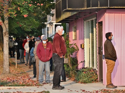 Looking west at the corner of 6th and Madison in Bloomington, Indiana. Voters are standing in line to cast their ballots at Election Central at 7th and Madison in Bloomington, Indiana on the first day of early voting, Oct. 6, 2020.