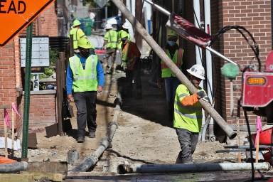A crew from E & B Paving work on the alley between 7th and 6th streets on the block between Washington and Walnut on Oct. 16, 2020. (Dave Askins/Square Beacon)