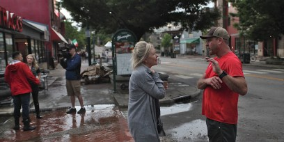 Mary Catherine Carmichael, Bloomington's director of public engagement, talks with Village Deli owner Bob Costello the morning after flooding left the deli's basement filled with 6 feet of water.