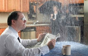 picture of a guy sitting in his kitchen with water raining in from the leaky ceiling for medina roofing