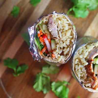 a burrito with rice, pork, carrots, cucumber, cilantro, and radishes