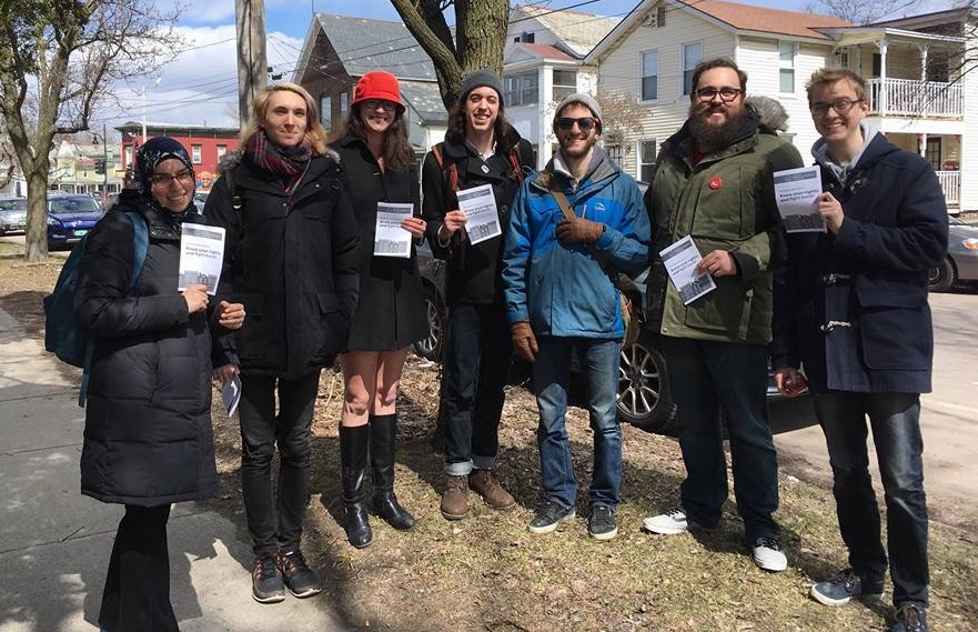 DSA Members stand together holding copies of the renters' rights pamphlet