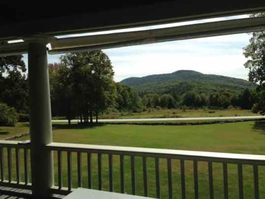 From the porch outside the studio the lawns slope down towards open fields and a view of the mountains. Photo by Kate Abbott