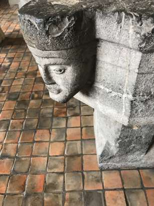 Faces peer out from a stone baptismal font. Photo by Kate Abbott