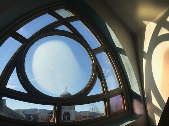 On the balcony of Goodrick Hall, a tricorn window looks out at Lasell Gymnasium and the top of Spring Street at Williams College. Photo by Kate Abbott