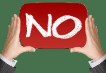 afbeelding van twee handen met een rood bord met daarop NO in het wit nee