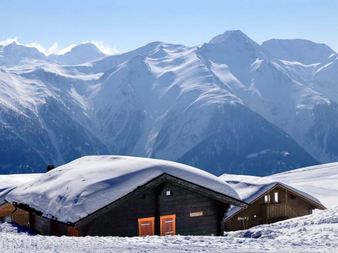 Alpenchalet op Fiescheralp in sneeuw met bergen op achtergrond