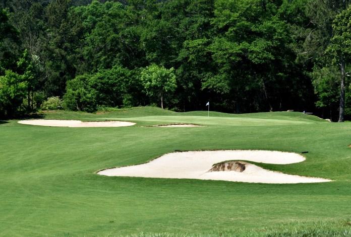golfbaan met bunker zand en hole tegen achtergrond van bomen
