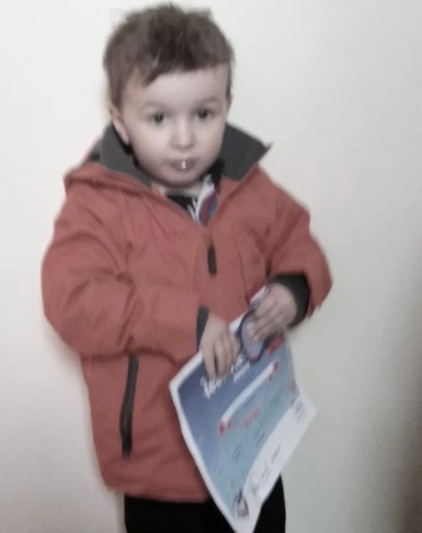 Boy in coat with ASA stage 1 swimming certificate