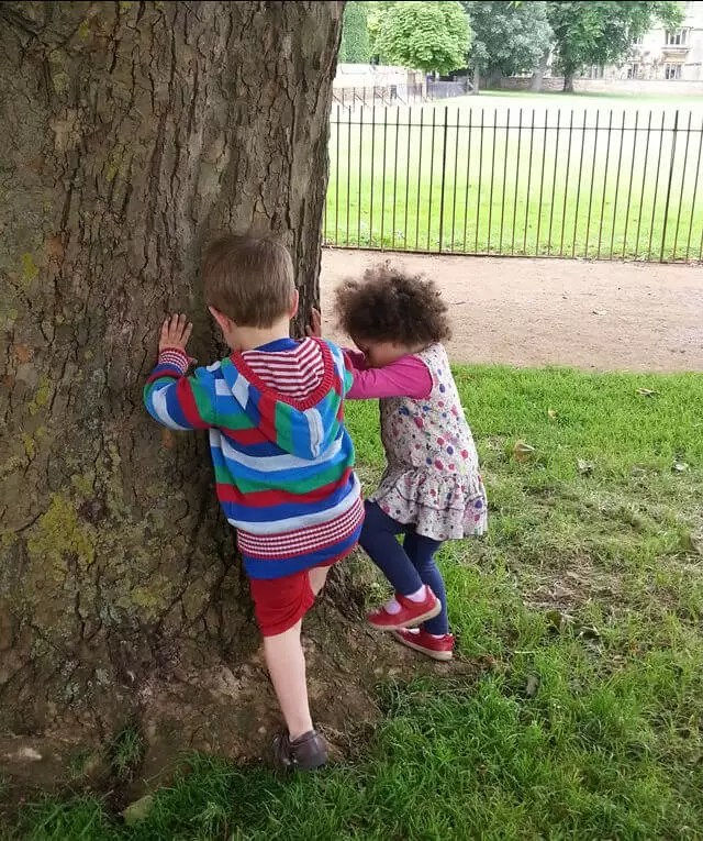 2 toddlers trying-to-climb-a-huge-tree