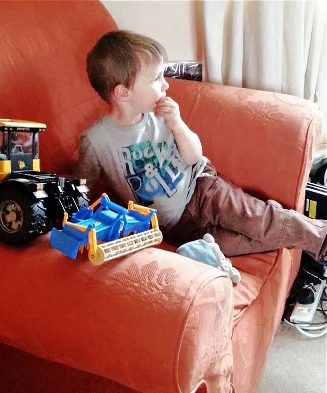 toddler sitting on orange comfy chair with toy tractor next to him on the chair arm