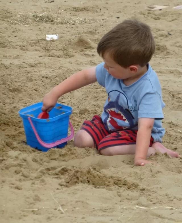 filling buckets on a sandy beach
