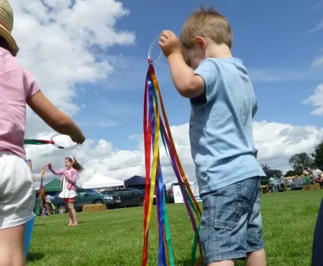 toddler playing with rainbow ribbons