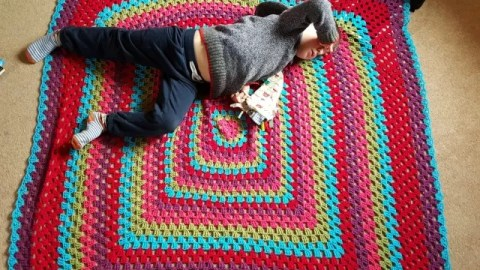 Bright Granny Square blanket and sprawling child