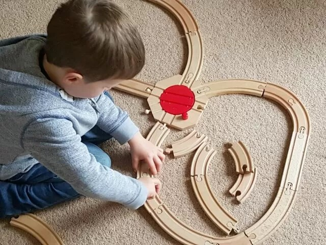 setting up a wooden train set