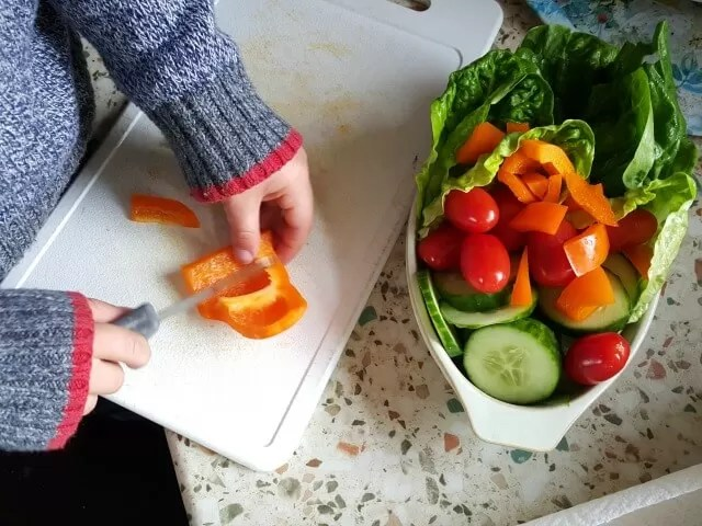 little boy chopping veg for a salad