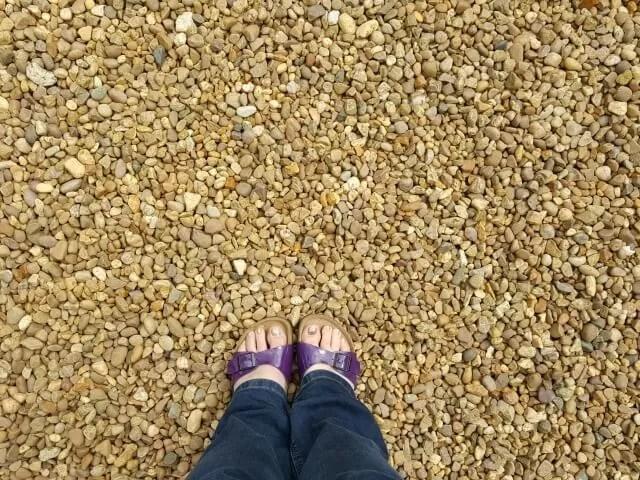 purple birkenstocks on gravel