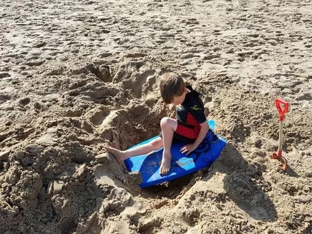 resting in a hole at the beach