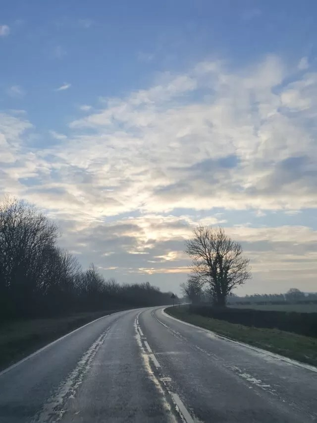 road leading into the distance and blue cloudy skies